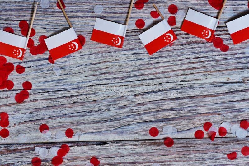 День независимости Сингапура 9-ое августа концепция свободы, независимости и патриотизма мини флаги с confetti на деревянном стоковое изображение rf