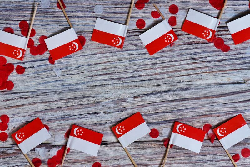 День независимости Сингапура 9-ое августа концепция свободы, независимости и патриотизма мини флаги с confetti на деревянном стоковое фото