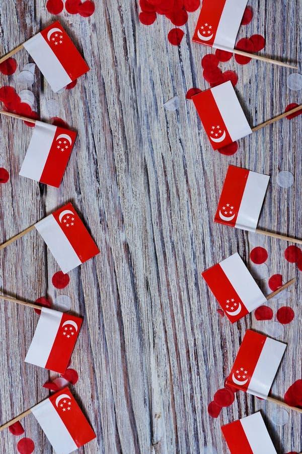День независимости Сингапура 9-ое августа концепция свободы, независимости и патриотизма мини флаги с confetti на деревянном стоковые фото