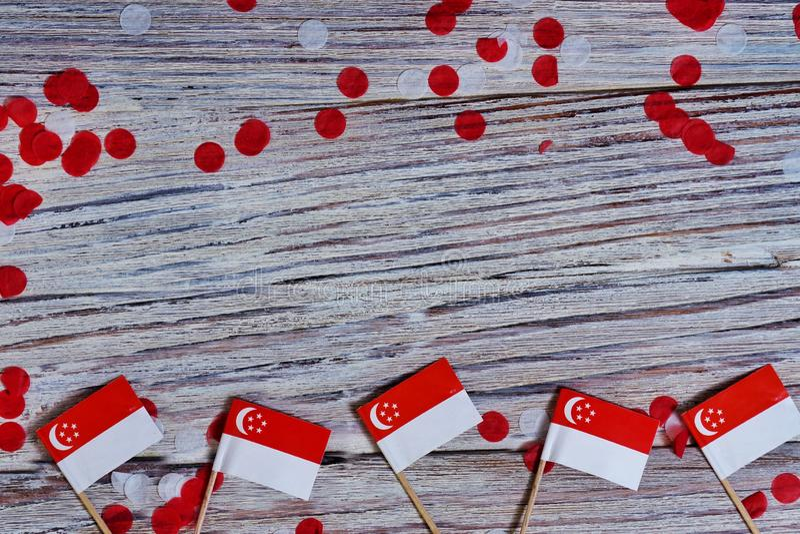 День независимости Сингапура 9-ое августа концепция свободы, независимости и патриотизма мини флаги с confetti на деревянном стоковая фотография rf
