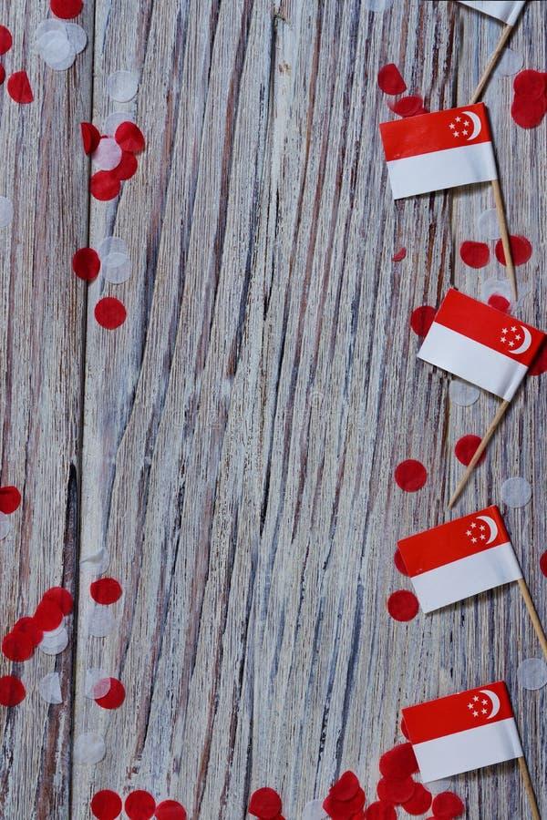 День независимости Сингапура 9-ое августа концепция свободы, независимости и патриотизма мини флаги с confetti на деревянном стоковая фотография