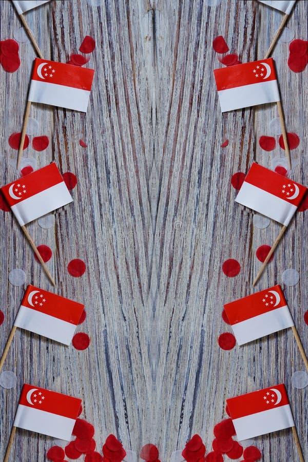 День независимости Сингапура 9-ое августа концепция свободы, независимости и патриотизма мини флаги с confetti на деревянном стоковые изображения