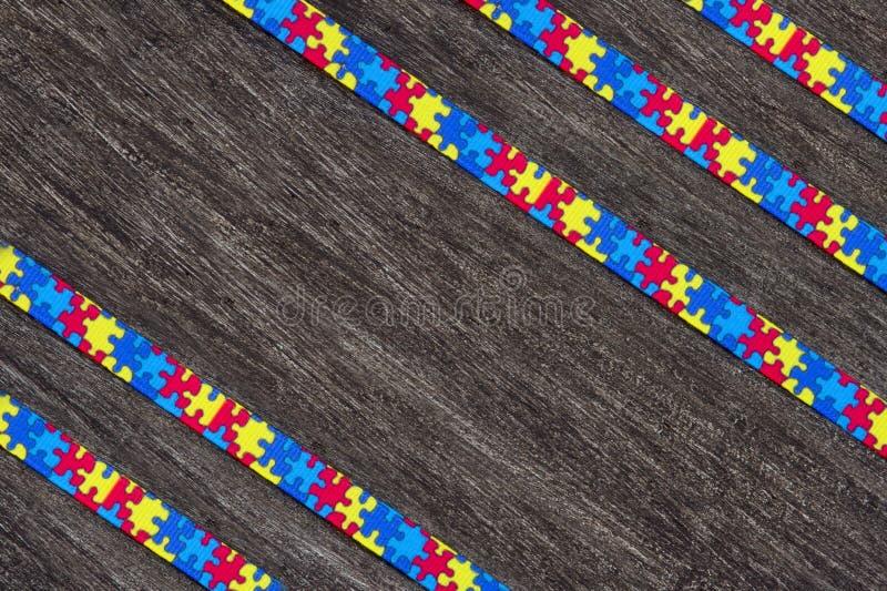 День осведомленности аутизма мира с лентой головоломки на деревянной предпосылке стоковое фото