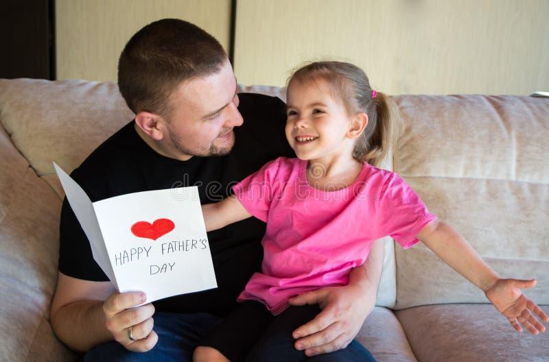 День отца Счастливая дочь семьи давая папе поздравительную открытку на празднике стоковые фотографии rf