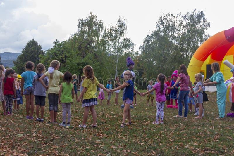 День праздника деревни со спортивными площадками аниматоров и детей и конкуренций в парке осенью стоковое изображение rf