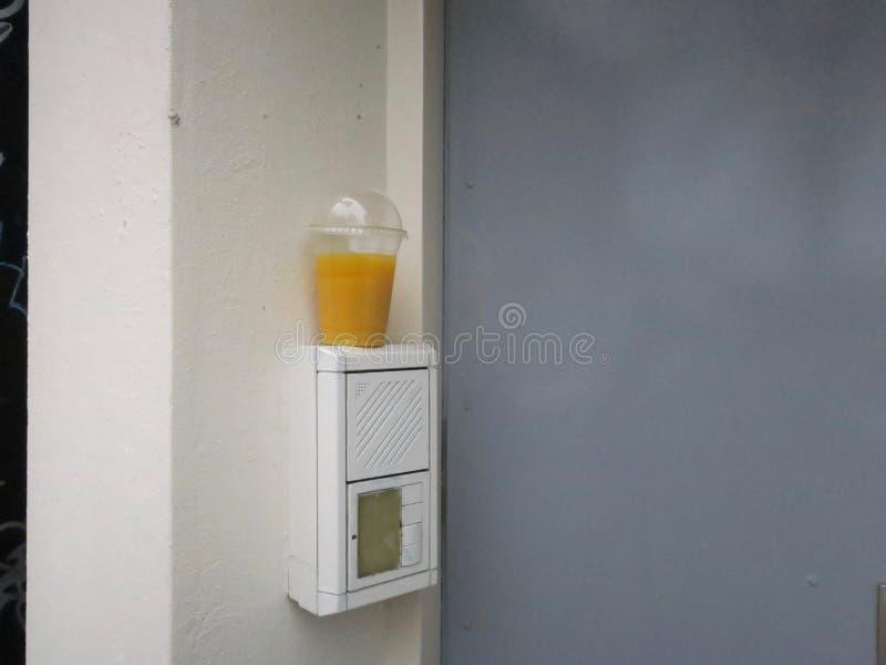 День сока, пластиковая чашка апельсинового сока выведенная около парадного входа стоковое изображение rf