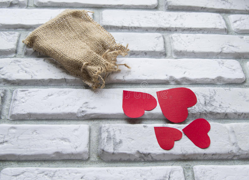 День ` s валентинки, красная сумка холста сердец, кирпичная стена белизны предпосылки стоковое изображение