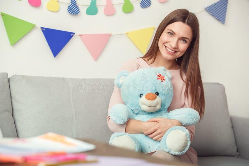 День ` s матери концепции торжества молодой женщины дома сидя держащ плюшевый медвежонка стоковые фотографии rf