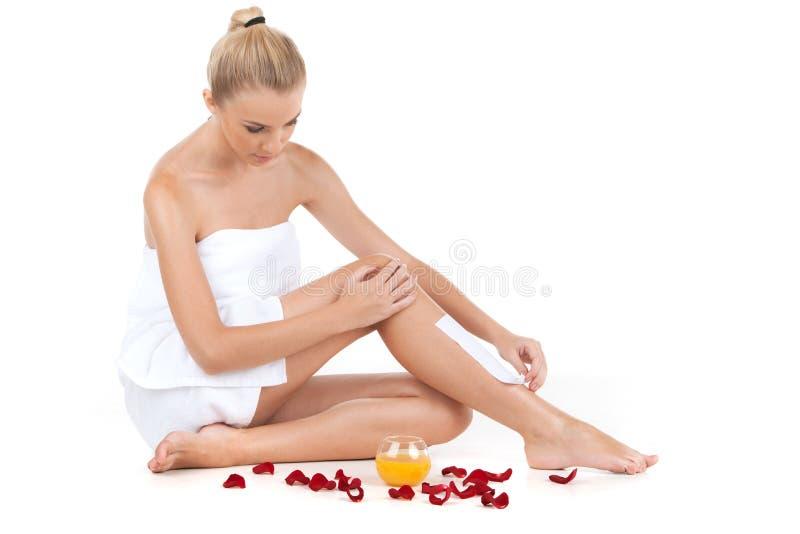 Депиляция женских ног с вощить на белой предпосылке стоковое фото