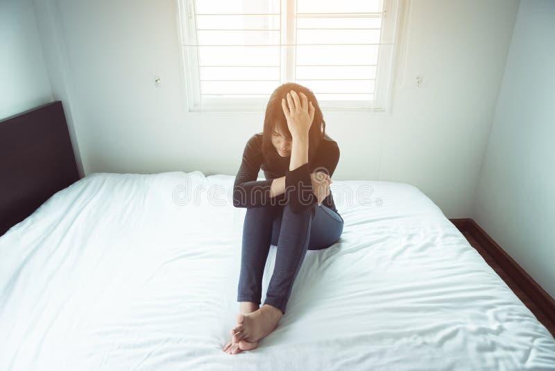 Депрессия женщины имеет тоскливость головной боли и чувства после бодрствования вверх в спальне стоковые изображения rf