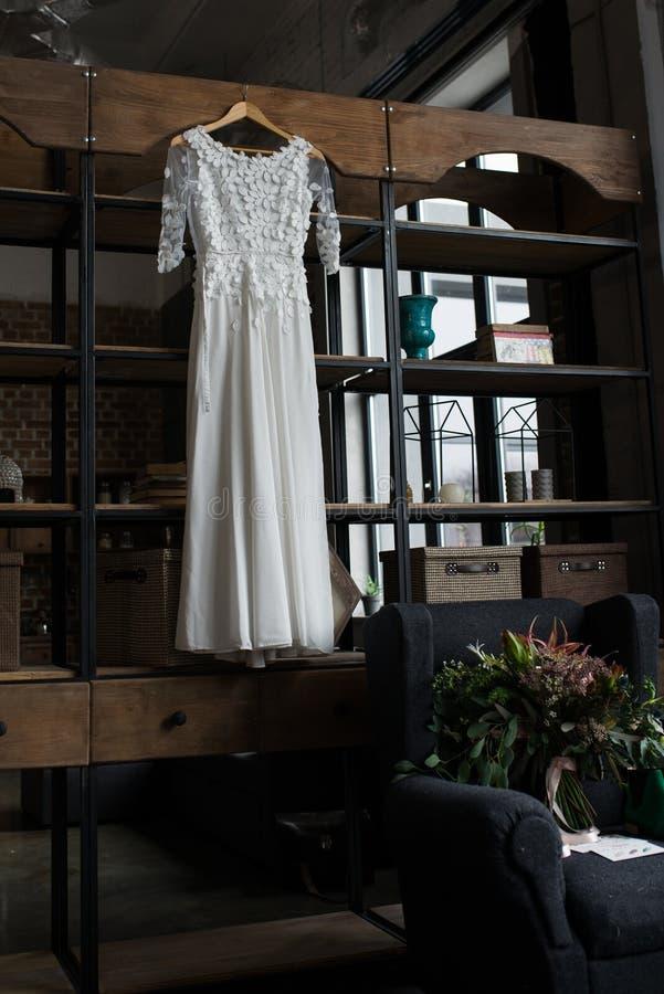 Деревенская белая смертная казнь через повешение платья свадьбы на кухонном шкафе просторная квартира конструкции нутряная самомо стоковое изображение rf