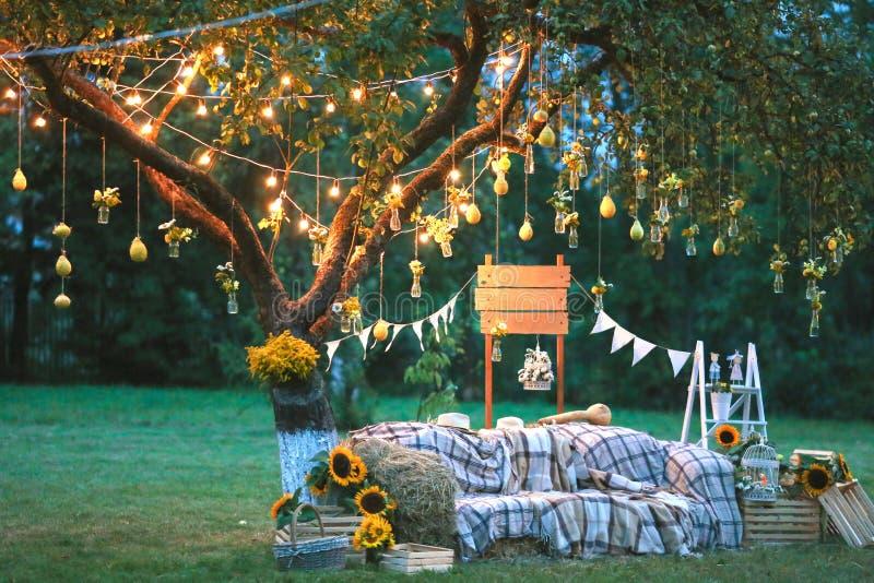 Деревенская зона фото свадьбы Ручной работы украшения свадьбы включают будочку фото, деревянные бочонки и коробки, фонарики, чемо стоковое изображение
