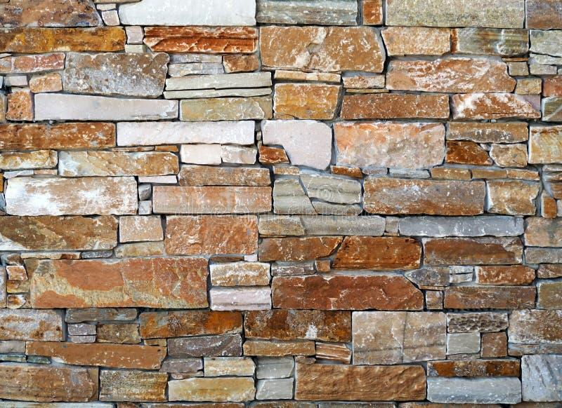 Деревенская каменная стена сделанная скачками кирпичей с различным размером, геометрически аранжированный в горизонтальных строка стоковое изображение