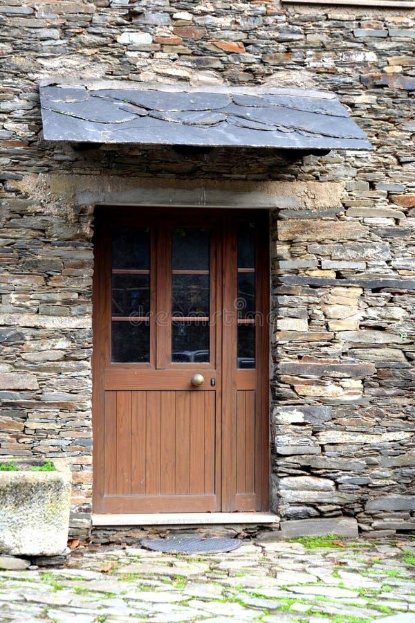 Деревенская рук-срубленная деревянная дверь установила в каменную стену построенную от сланца в Piodão, сделанном стога утесов сл стоковое фото