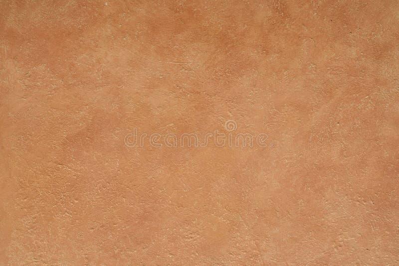 Деревенская текстурированная штукатурка покрашенная терракотой стоковое фото rf