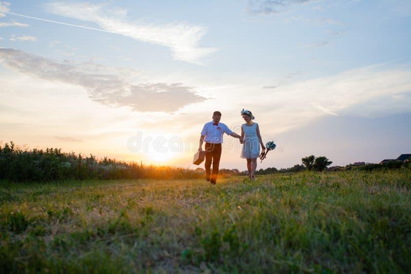 Деревенские пары свадьбы на заходе солнца в поле стоковые фотографии rf