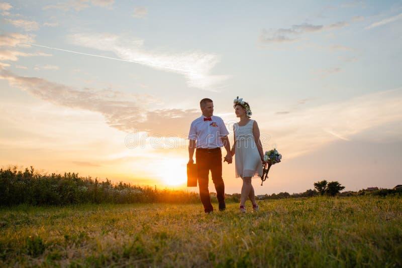 Деревенские пары свадьбы на заходе солнца в поле стоковые изображения rf