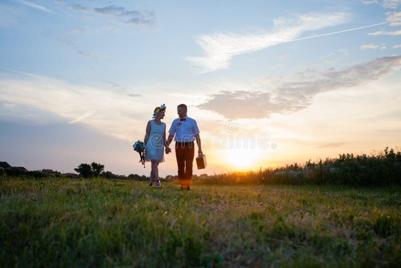 Деревенские пары свадьбы на заходе солнца в поле стоковая фотография