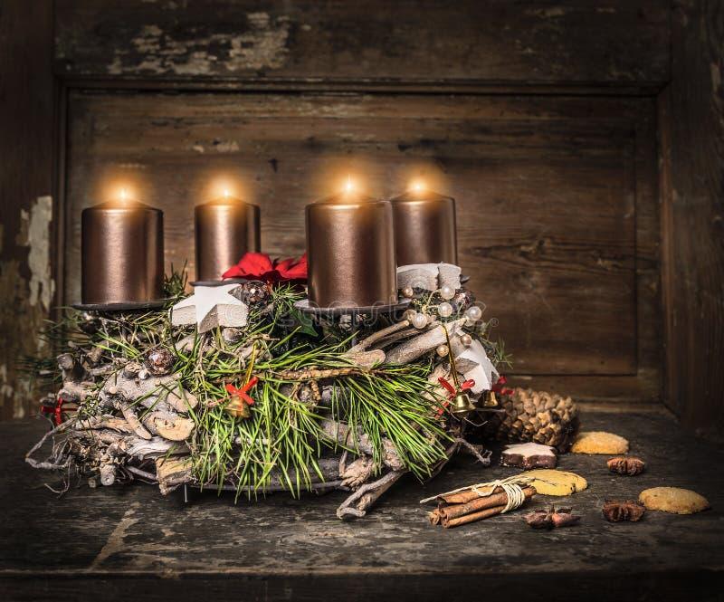 Деревенский венок пришествия с 4 горящими свечами и традиционным печеньем стоковые изображения rf