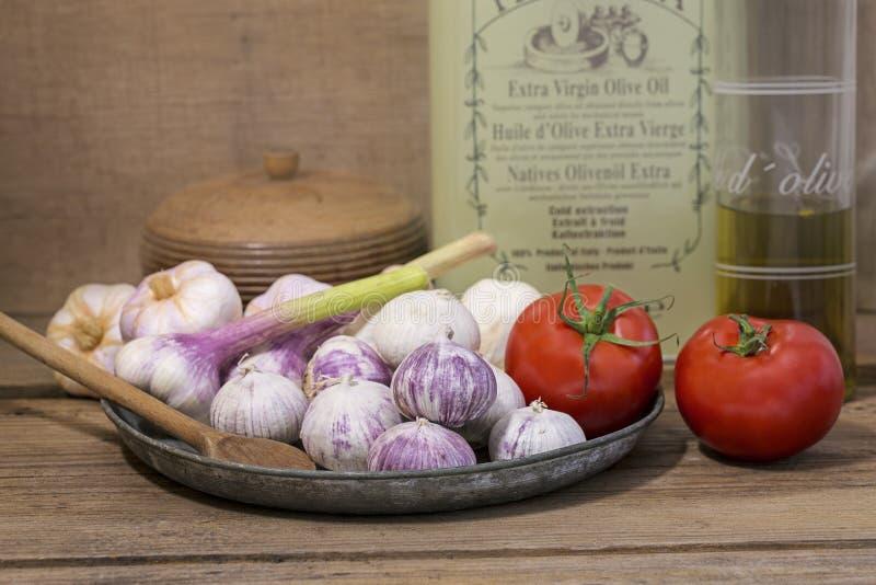 Деревенский среднеземноморской натюрморт кухни с маслом, томатами и чесноком стоковые фотографии rf