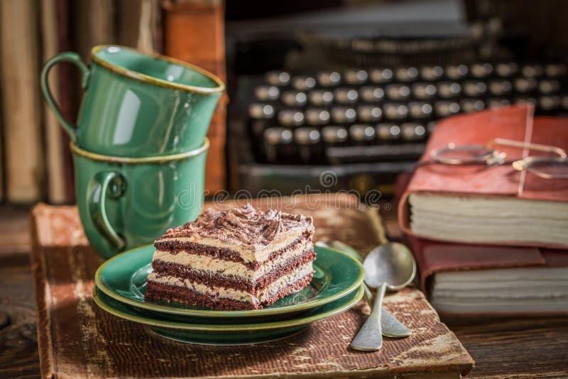Деревенский шоколадный торт и кофе с книгами и машинкой стоковое фото rf