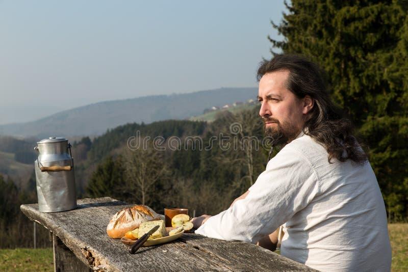 Деревенски длинн-с волосами человек snacking здоровая еда стоковые изображения rf