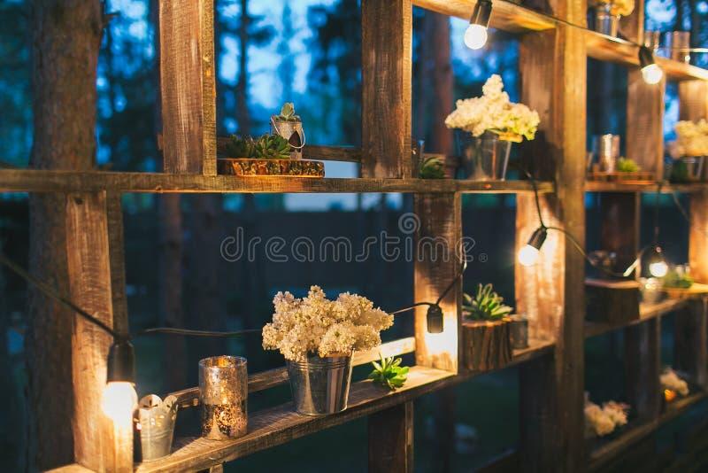 Деревенское оформление свадьбы, стойка полки с расположениями сирени и su стоковое изображение rf