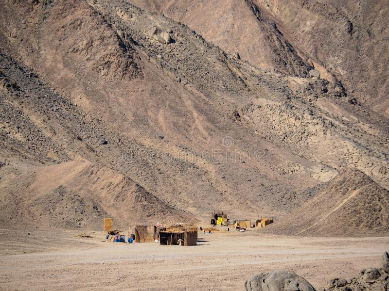 Деревня бедуин перед возвышенными холмами, вид на долгую перспективу Дезерт Египта в феврале Серое горное лицо в пустыне Селектив стоковая фотография