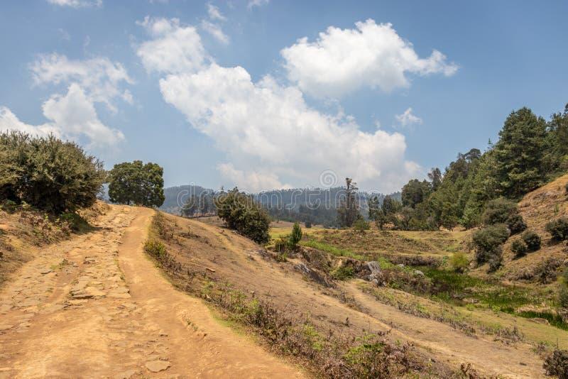 Деревня отголоска с ведущей дорогой и голубым небом стоковая фотография