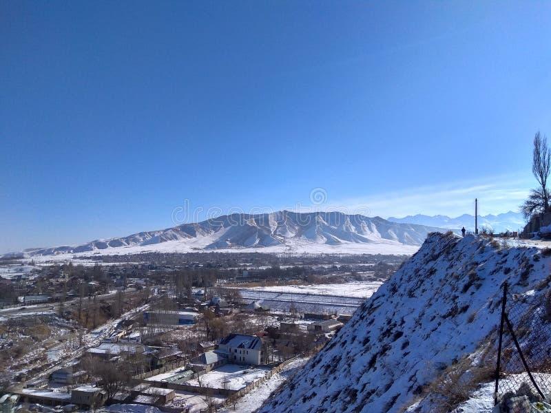 деревня спрятанная между горами в зиме стоковое изображение rf