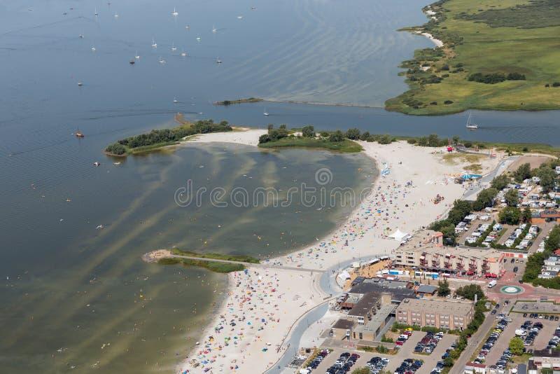 Деревня Makkum вида с воздуха голландская с пляжем и людьми заплывания стоковые фото