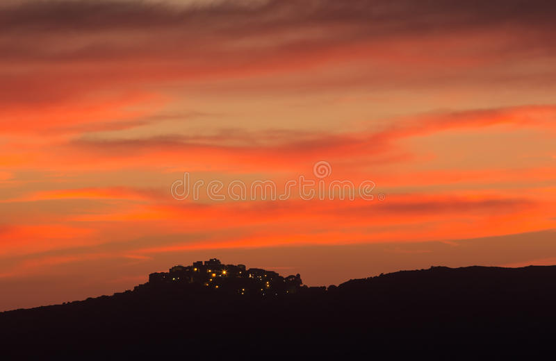 Деревня Sant Antonino в Корсике silhoutted против розового кануна стоковые фотографии rf
