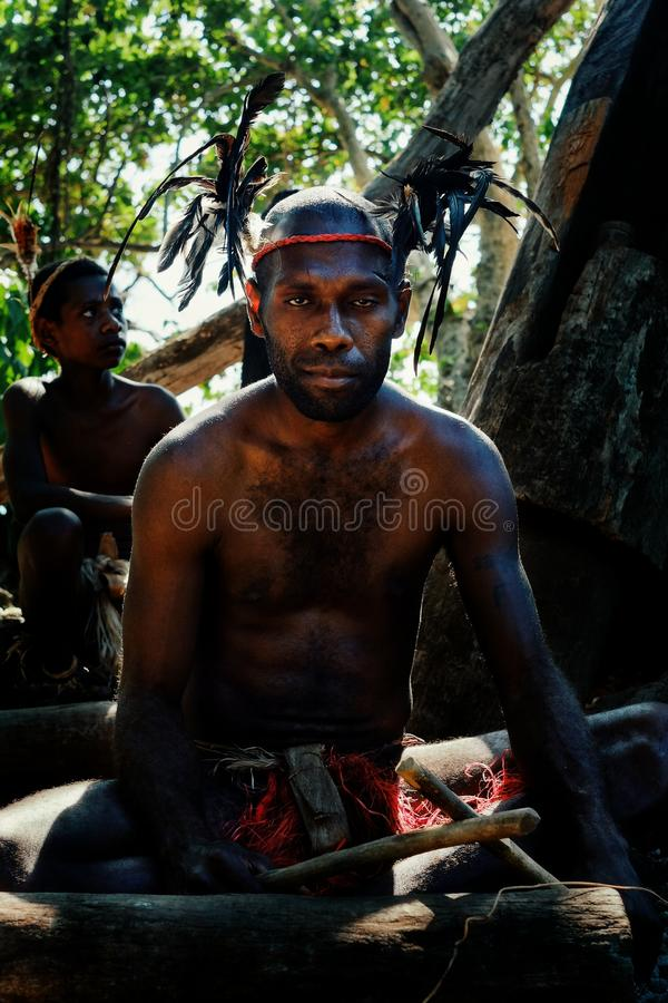 Деревня Walarano, остров Malekula/Вануату - 9-ОЕ ИЮЛЯ 2016: местный племенной человек барабаня в головном уборе пера во время дер стоковое фото
