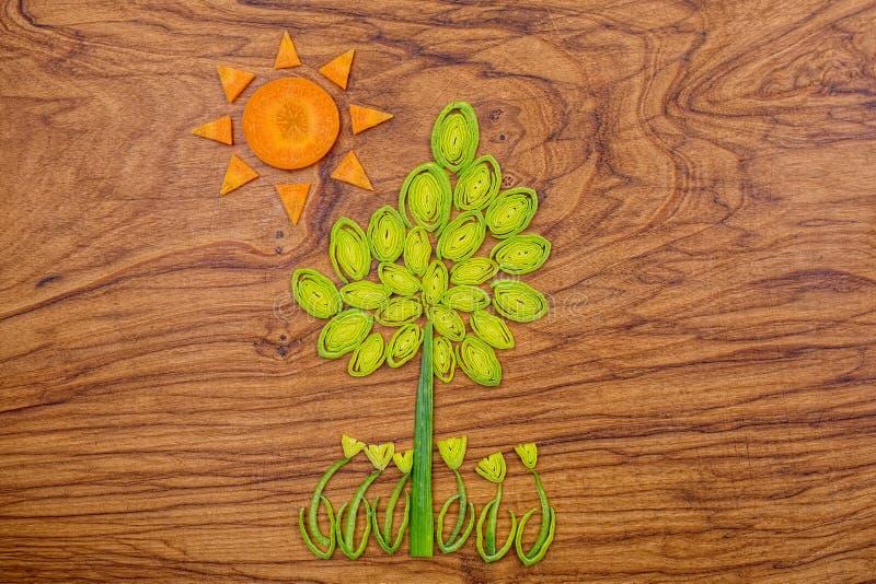Дерево, цветки и солнце сделанные лук-порея и кусков моркови на деревянной предпосылке разделочной доски стоковые изображения rf