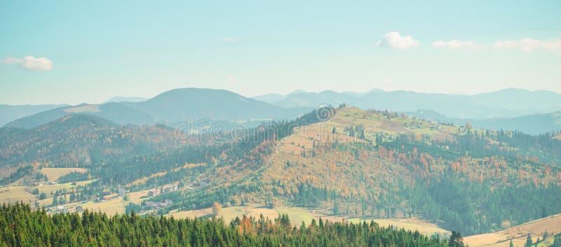 Деревья, покрытые с листьями желтых и шарлаха, на которых падения греют светлые горы Прикарпатско, Украин Сцена деревни осени стоковые изображения