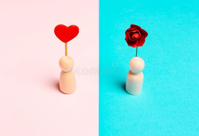 Деревянка с сердцем и мужчиной с цветком на розовом фоне стоковое изображение rf