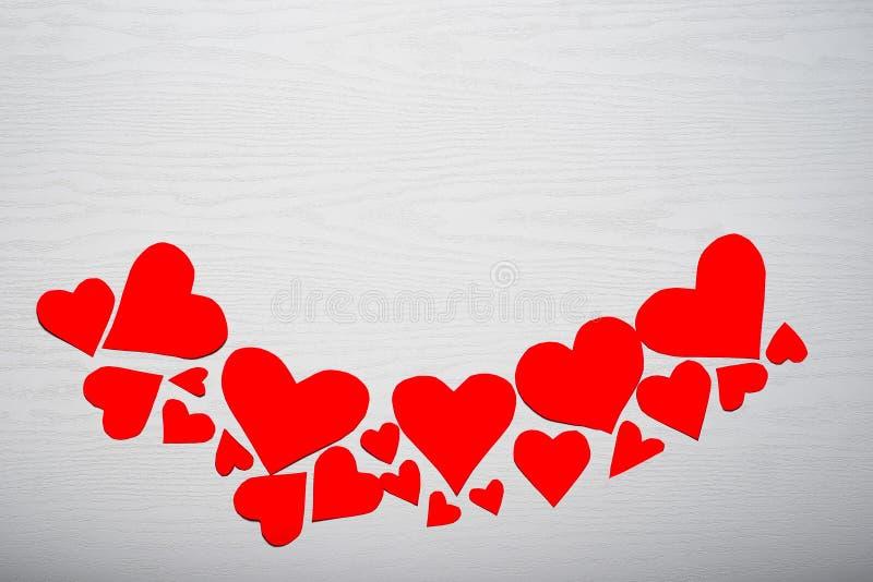 Деревянная белая предпосылка с красными сердцами Концепция Valentin стоковые изображения