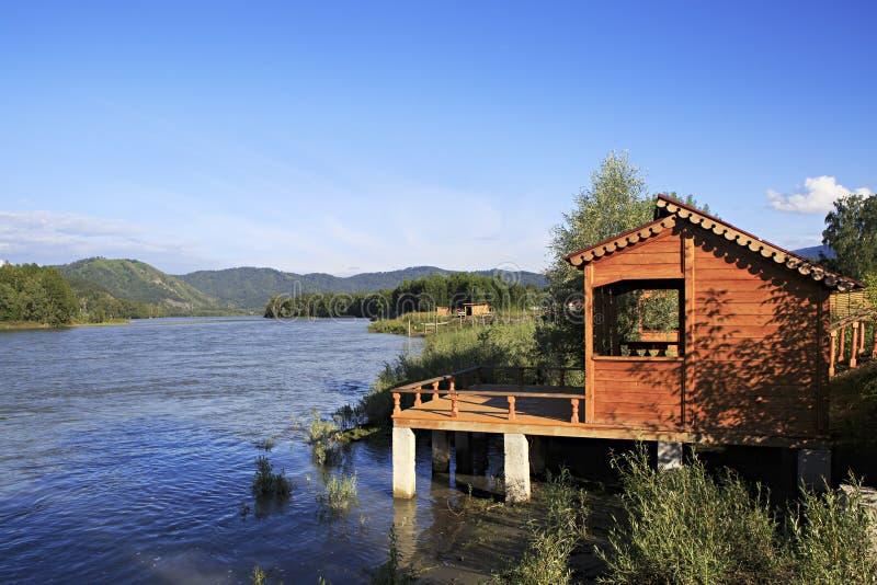 Деревянная веранда на реке Katun горы стоковое изображение