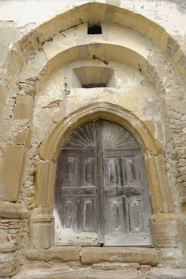 Деревянная дверь в высекаенной, каменной стене, конематке Copsa, Румынии стоковое фото rf