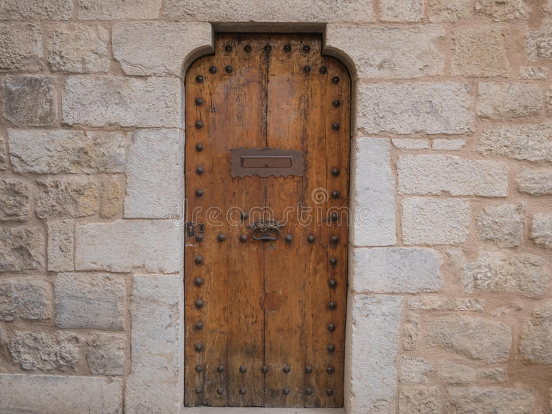 Деревянная дверь с ручкой металла, каменной стеной стоковое фото