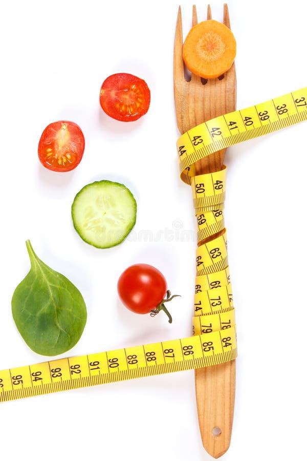 Деревянная вилка обернула рулетку и свежие зрелые овощи, концепцию уменьшения и здоровое питание стоковое изображение rf