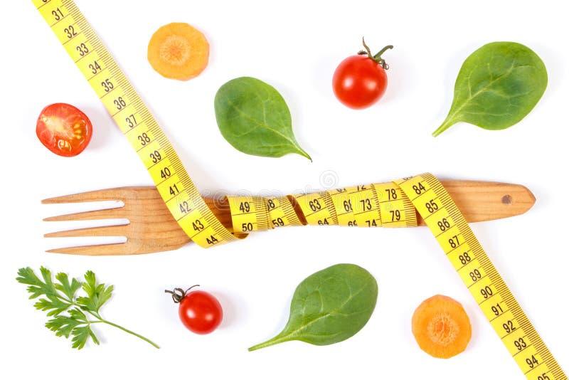 Деревянная вилка обернула сантиметр и свежие овощи, концепцию уменьшения и здоровое питание стоковая фотография