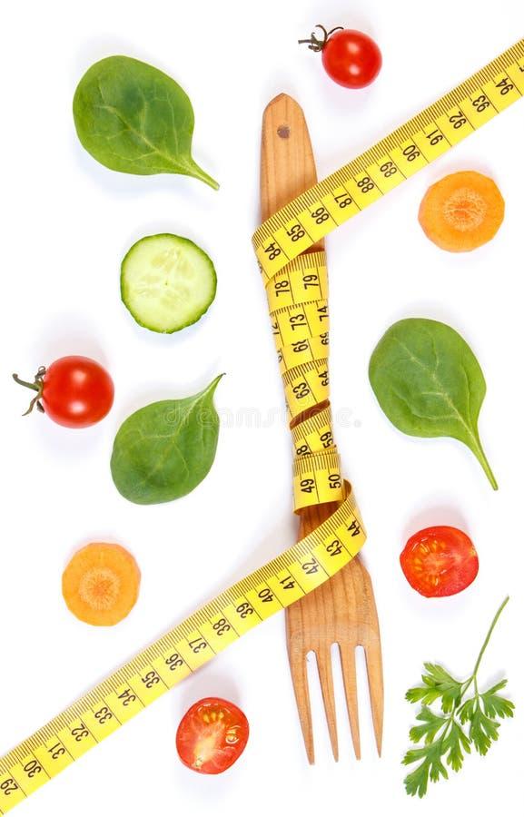 Деревянная вилка обернула сантиметр и свежие овощи, концепцию уменьшения и здоровое питание стоковые изображения rf