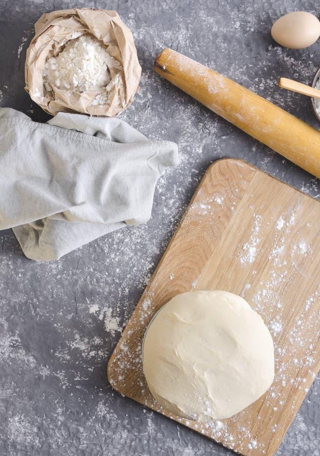 Деревянная вращающая ось, мука в бумажном мешке, яйца, салфетка и поднятое тесто на деревянной разделочной доске, взгляд сверху С стоковое фото rf