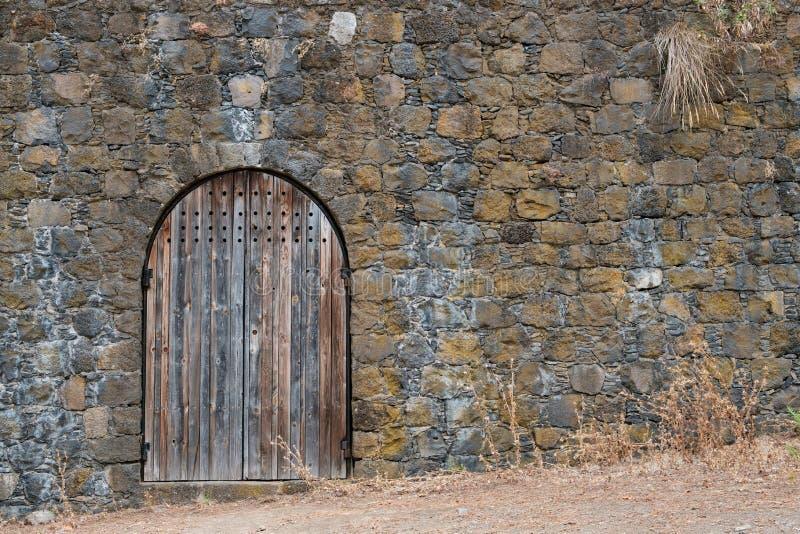Деревянная дверь/винтажные деревянные ворота на естественной каменной стене - стоковая фотография rf