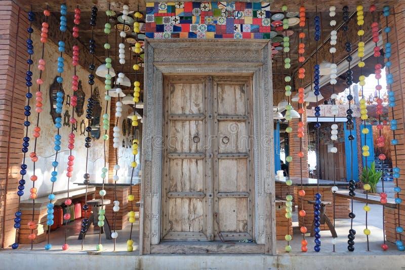 Деревянная дверь украшенная с яркими цветами стоковое изображение