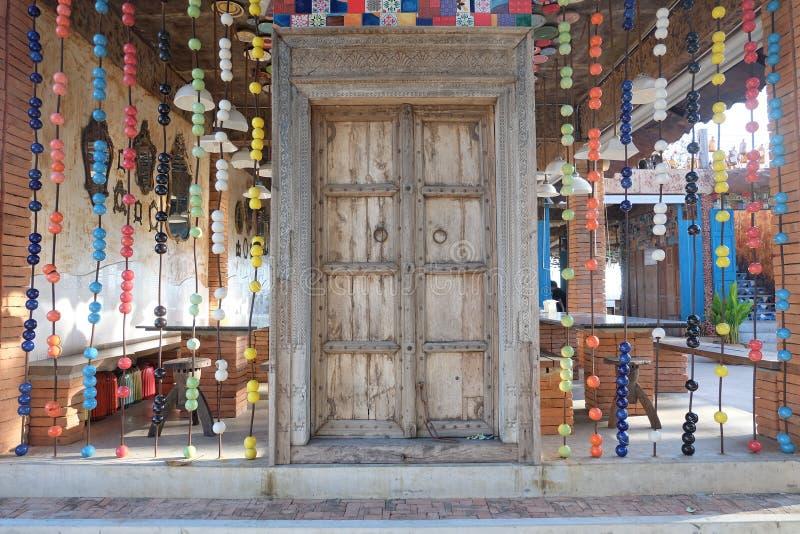 Деревянная дверь украшенная с яркими цветами стоковые фото