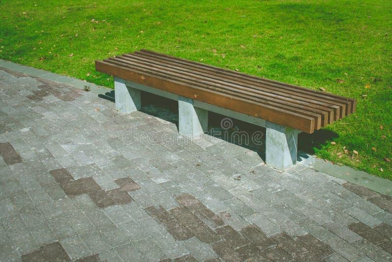 Деревянная длинная установка стенда на конкретной дорожке около поля луга зеленой травы на общественном парке стоковые изображения rf