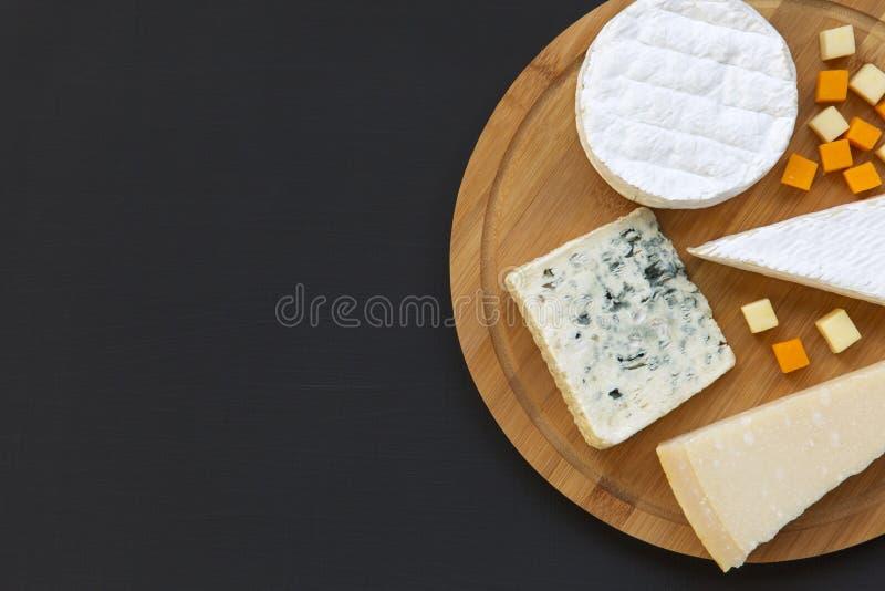 Деревянная доска с различными типами сыра, взгляд сверху Темная предпосылка Космос для текста стоковые фото