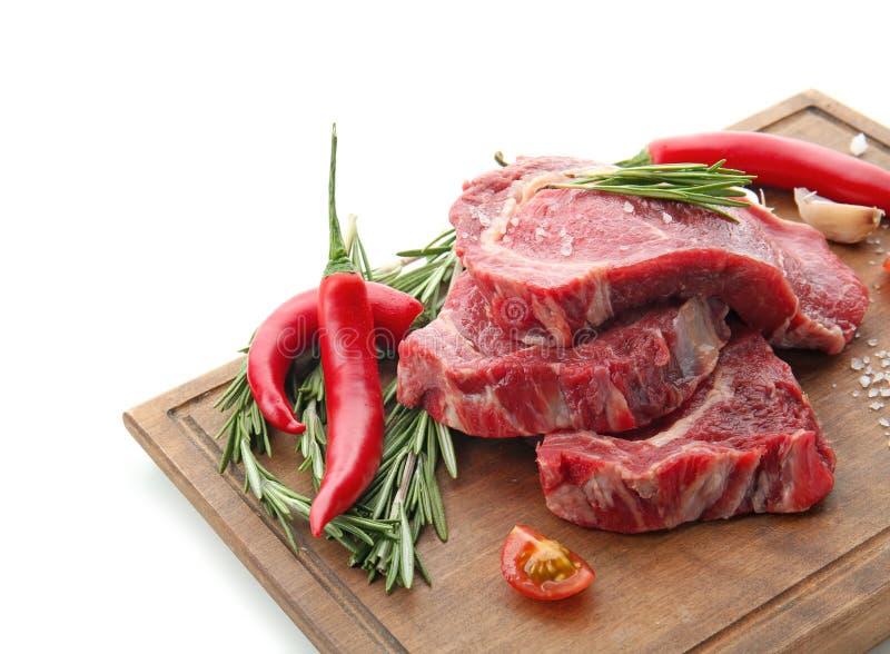 Деревянная доска с сырым мясом и свежими специями и томатами на белой предпосылке стоковое фото rf